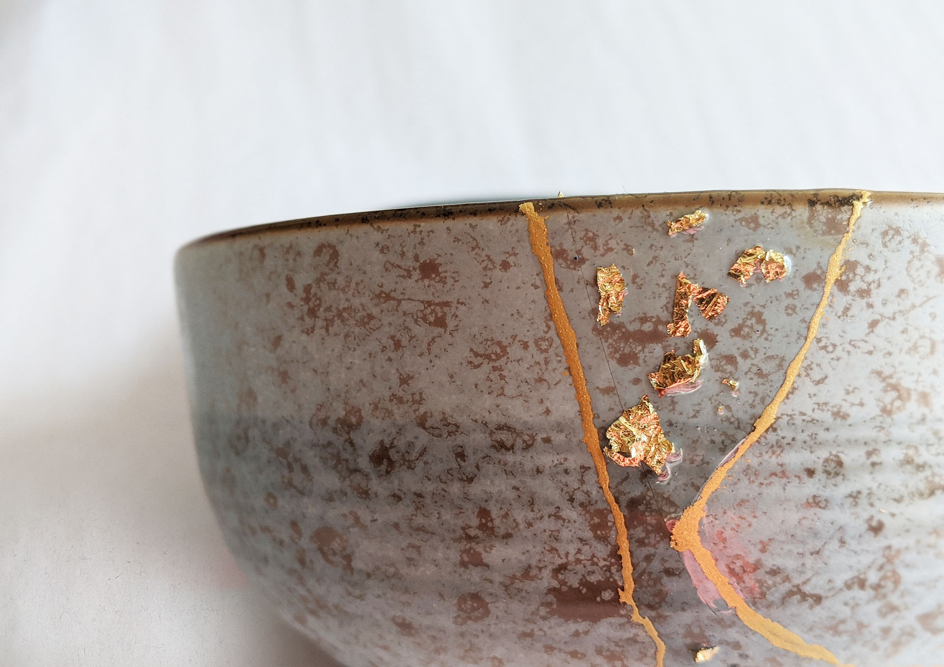 Kintsugi Repair: Gold color plus resin embedded with gold flakes by Fan Stanbrough